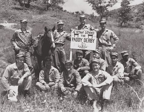 "Sergeant Reckless with Sgt. Lively's squad when they challenged the champion horse Native Dancer to race in the ""Paddy Derby"" at ""Upsan Downs"". Standing, L-R: Lt William Riley, Platoon Sgt. Joseph Latham, Corpsman Doc Mitchell, Sgt. John Lisenby. Seated, L-R: Edward Kujawa, PFC Joseph Gonlon, PFC Billy Jones, Sgt. Elmer Lively, PFC Monroe Coleman, CPL Kenneth Schumacher, PFC Jose Cordova, PFC Booker T. Crew"